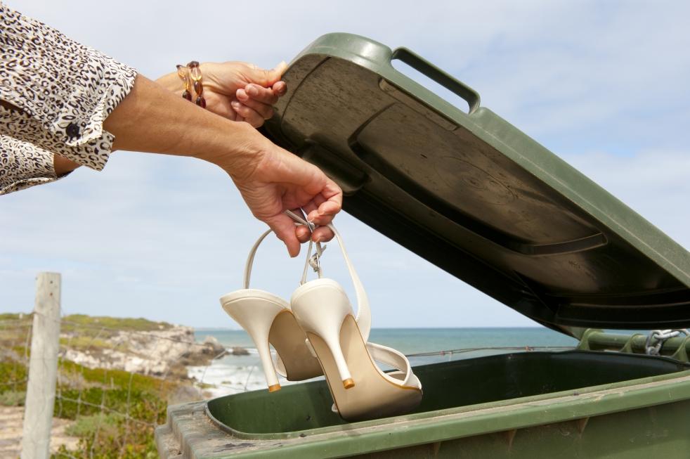 Frau wirft ihre Schuhe in die Mülltonne